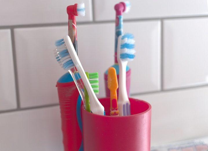 Variety of different coloured toothbrushes in a red cup against a white-tiled wall.