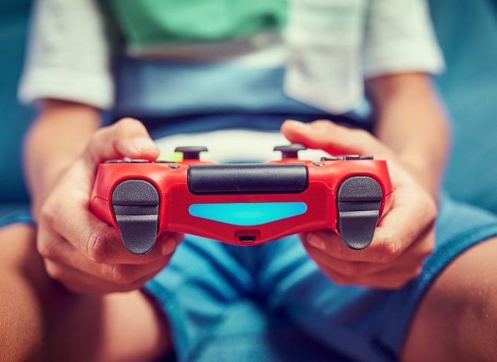 Child's hands holding a red PS4 controller.