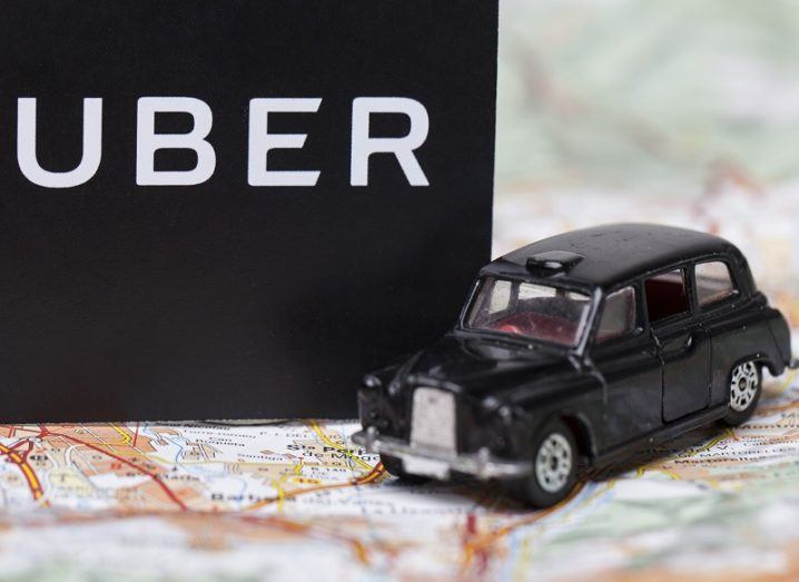 A black London taxi toy beside an Uber logo on a paper map.