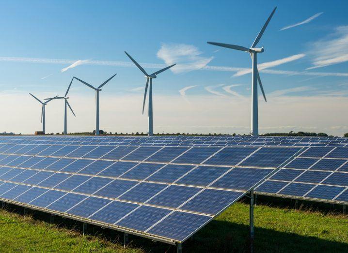 A solar farm and wind turbines on a sunny day.