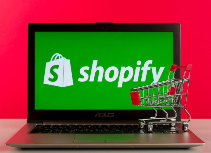 The Shopify logo is on a laptop with a toy shopping trolley against a red background.