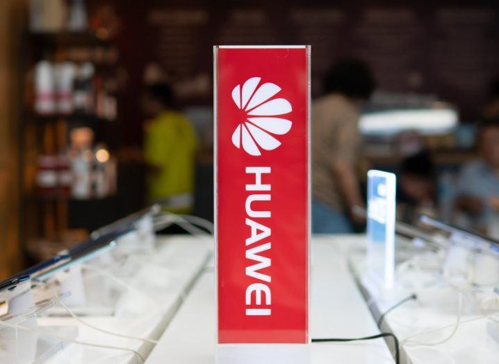 A Huawei sign on a glass table.