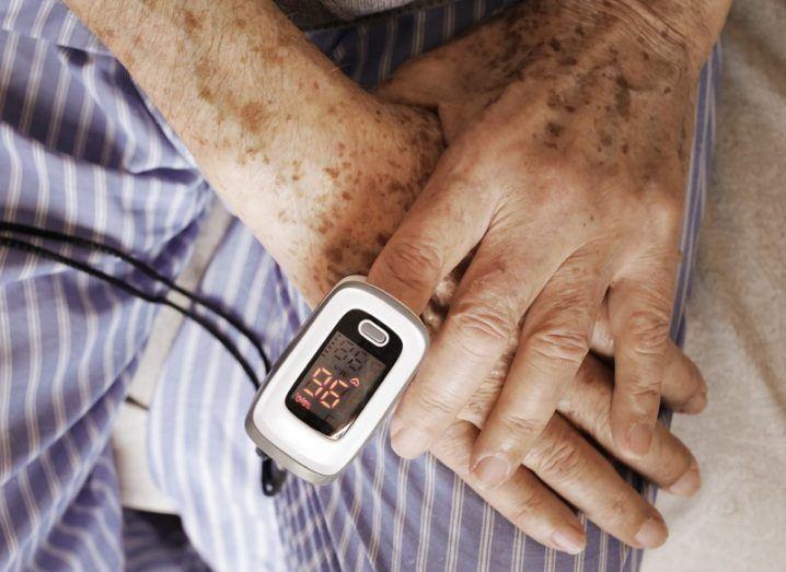 Blood-oxygen-level reader worn on an elderly man's finger.