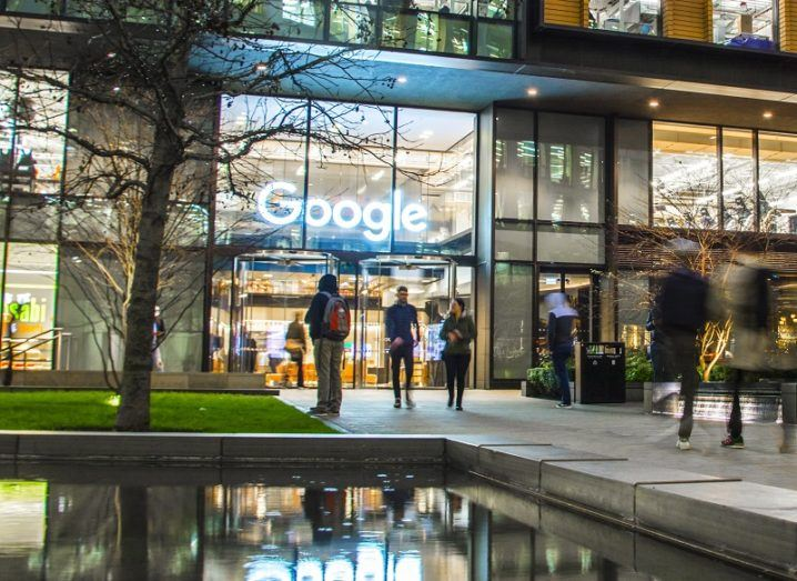 Exterior of Google's London office at night with people walking past.