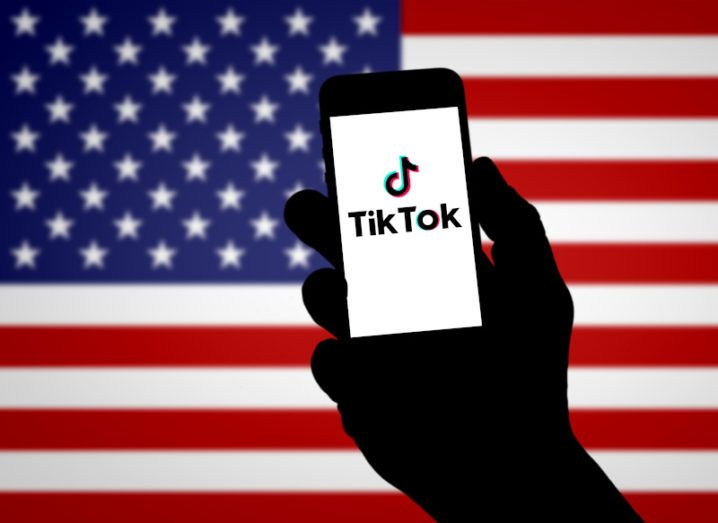 The silhouette of a hand holding up a smartphone displaying the TikTok logo against the backdrop of an American flag.