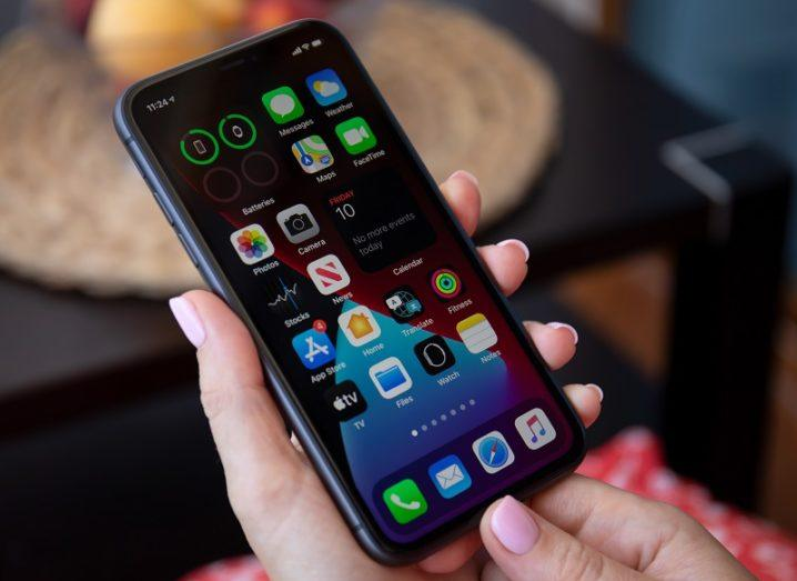 Hands of someone holding an iPhone with iOS 14.