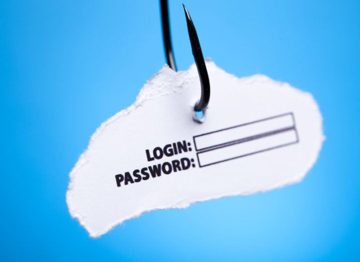 A fishing hook is hanging against a blue background with a piece of paper asking for login and password details, symbolising phishing and email scams.
