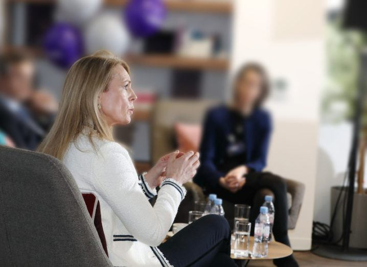 A side profile of a blonde woman wearing a black and white blazer sitting in a grey chair. She is speaking as part of a panel. The other panellists are blurred out in the background.