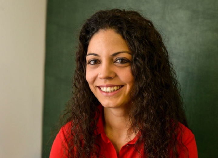 Araceli Venegas-Gomez smiling in a red shirt, sitting in front of a green and white wall.