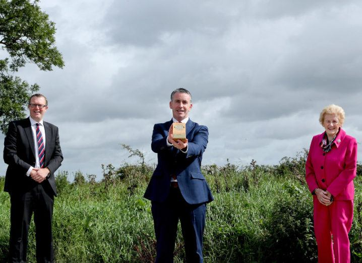 Two men and one woman are standing outside in a rural area and smiling into the camera for the announcement of the Enterprise Ireland Innovation Arena awards.