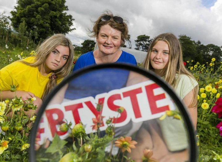 Ali Funge, Mari Cahalane and Clodagh Funge holding a BTYSTE sign in front of a microscope in a field with yellow flowers.