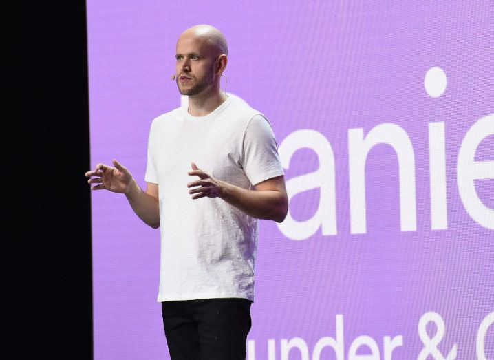 Daniel Ek stands on a stage wearing a white T-shirt, in front of a purple screen.