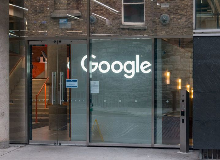 A large glass door to an office building. Inside the entrance is a white wall with the Google logo lit up in large letters.