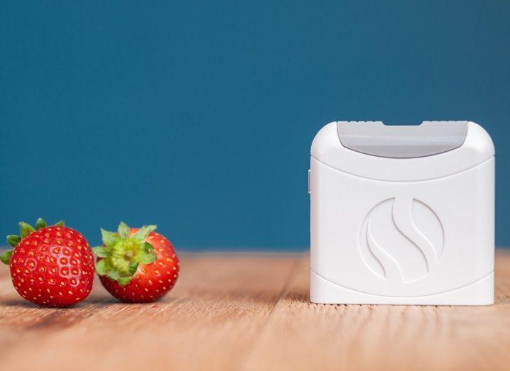 A FoodMarble device beside two strawberries on a wooden table against a blue background.