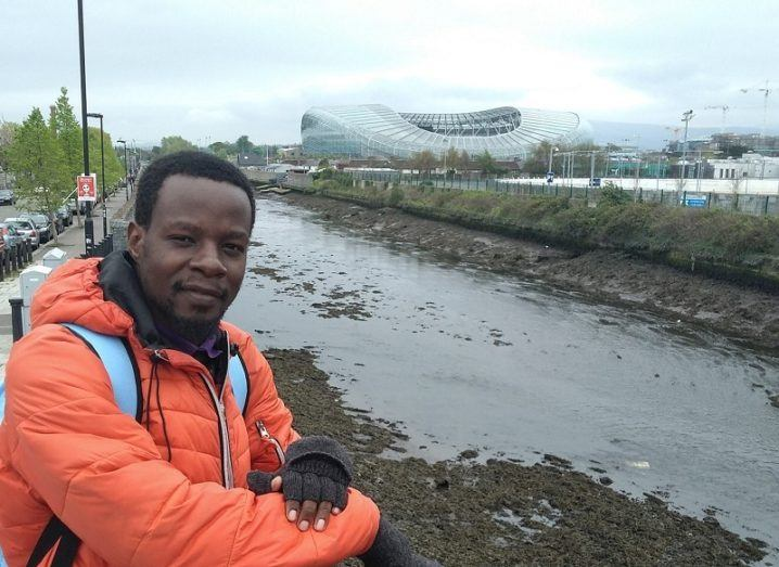 Fernandos Kredgie Ongolly in an orange jacket posing for a photo in front of the Aviva Stadium.