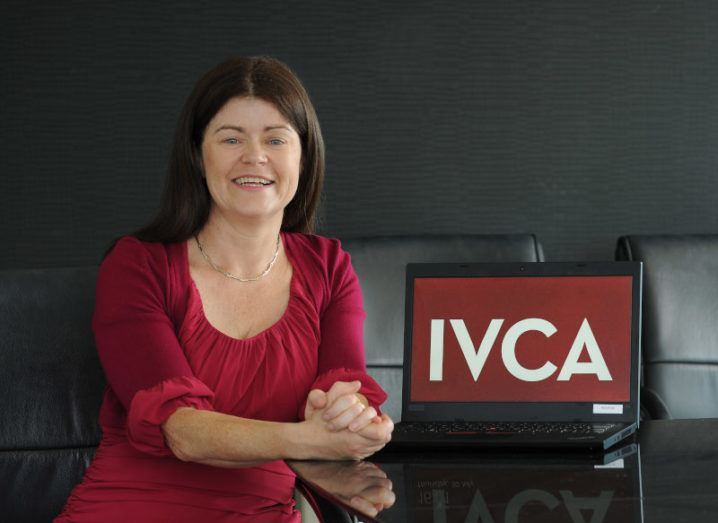 Gillian Buckley sits at a desk in a red dress, beside a laptop that says 'IVCA' on the screen.