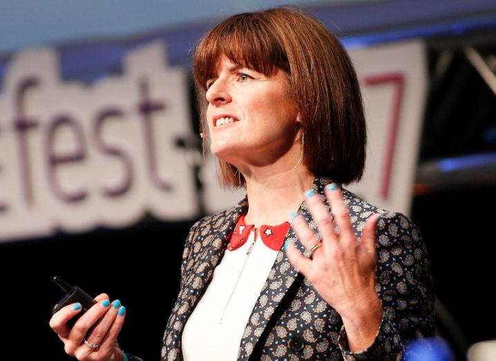 Adrienne Gormley, a woman with short brown hair wearing a patterned blazer, speaking on stage at Inspirefest 2017.
