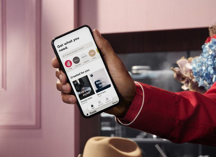 Hand holding a smartphone with the Klarna app open.