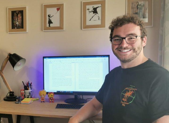 Michael O'Sullivan in a grey T-shirt smiling beside a PC on a desk.