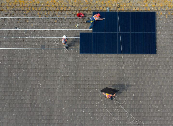 Top-down view of construction workers installing solar panels on a school roof.