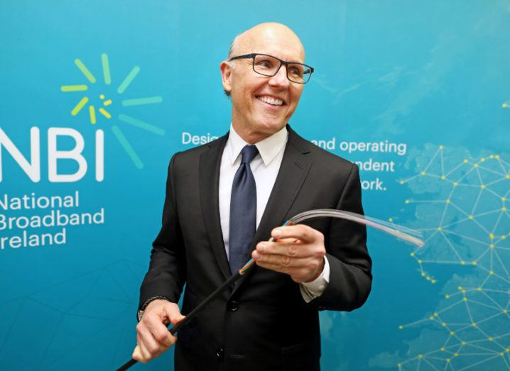 David McCourt stands in a suit holding a fibre cable in front of a sign that says National Broadband Ireland.
