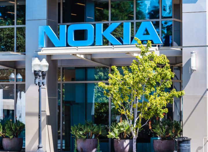 A large blue Nokia logo over the door of a glass office building on a sunny day, with a leafy tree to one side.