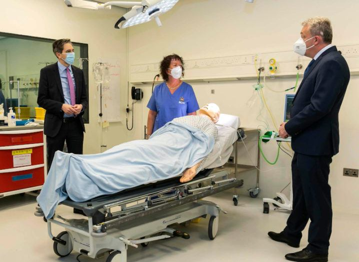 Two men in suits stand either side of a hospital bed with a dummy patient in it, while a woman doctor in scrubs stands in the middle closest to the bed. All three people are wearing face masks.