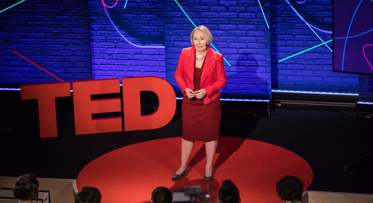 Dr Valerie Young is speaking to an audience about imposter syndrome on a stage with a TED sign.