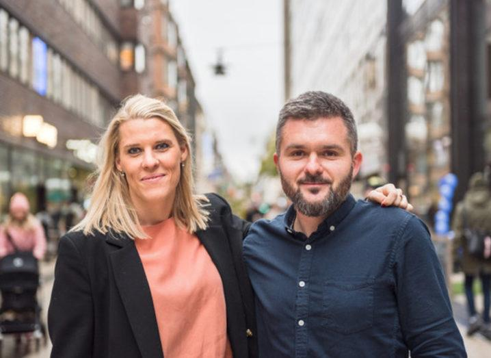 The co-founders of Teemyco are standing beside each other on an outdoor street and smiling into the camera.