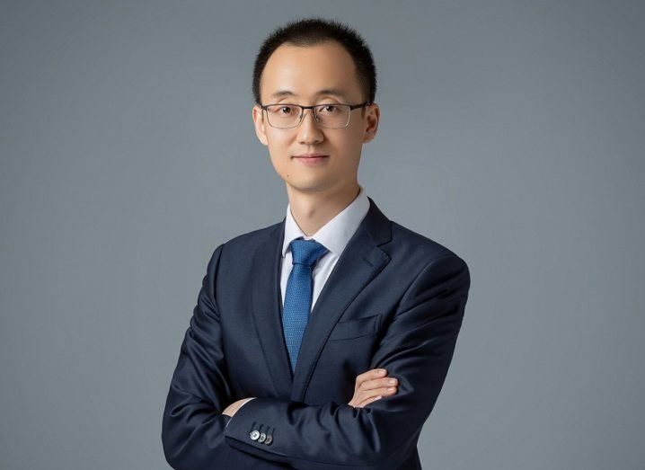 Tony Yangxu in a suit and tie crossing his arms against a grey background.