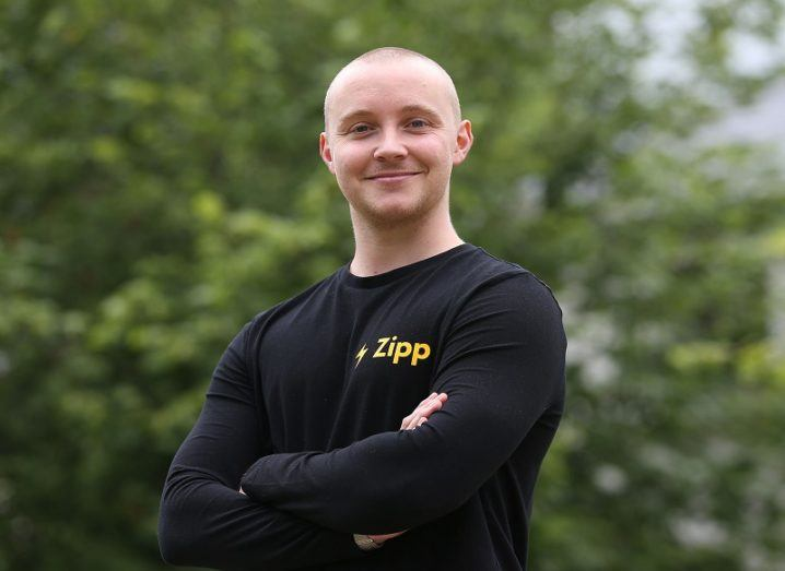 Zipp Mobility founder, Charlie Gleeson crossing his arms and smiling while standing against a leafy background.