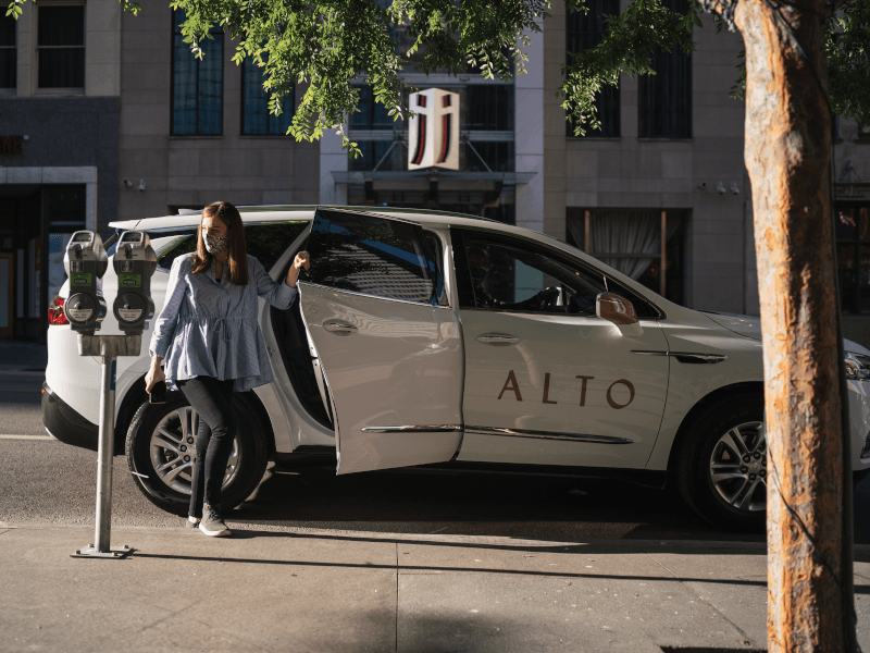 A woman wearing a mask exits an Alto car.