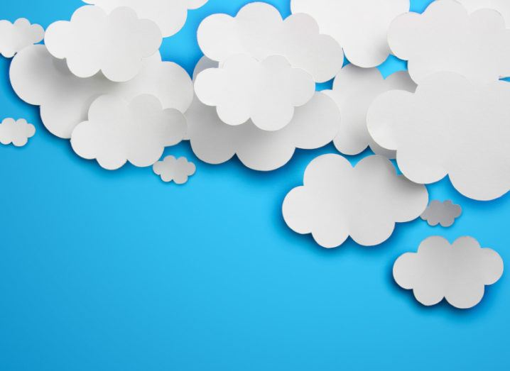 Clouds cut out of paper against a blue background, representing digital transformation and cloud computing.