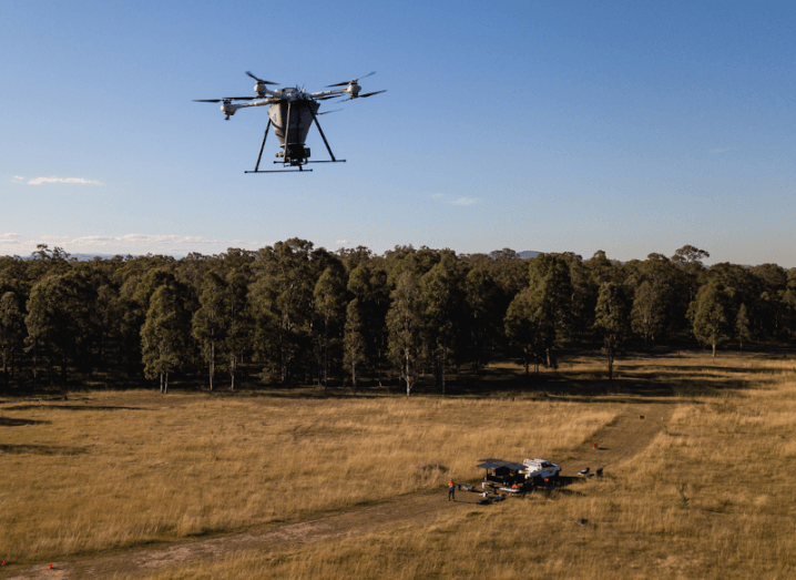 A drone flying over dry grass. There are trees in the background and the sky is blue.