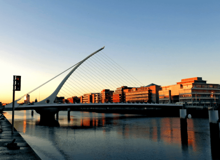 The Samuel Beckett bridge in Dublin city, with the sun setting in the background.