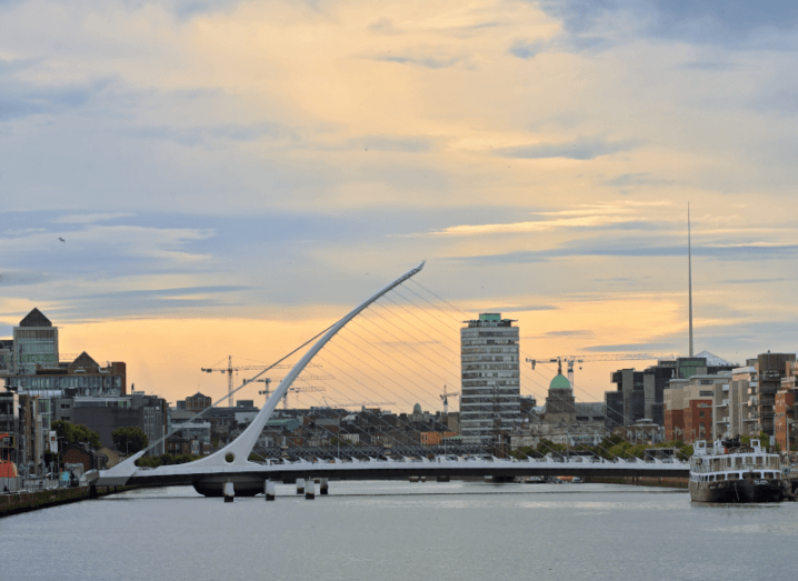 The Samuel Beckett bridge in Dublin city, with buildings and banks in the background.