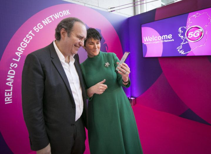A man in a suit and a woman in a green dress stand beside each other looking at a phone, in front of a screen that says '5G'.
