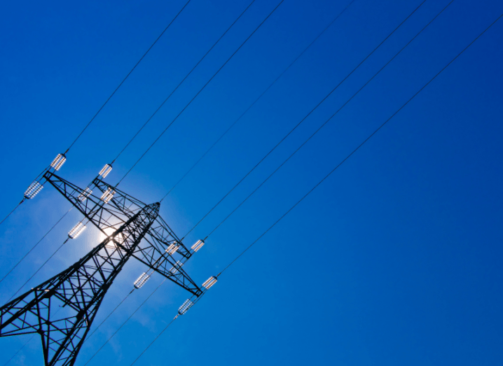 An electricity mast in front of a blue sky.