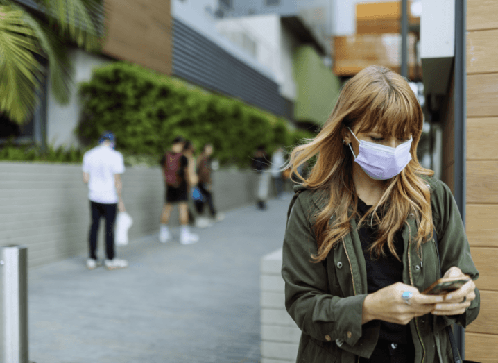A person wearing a green jacket and a white face mask standing in public, using a smartphone.