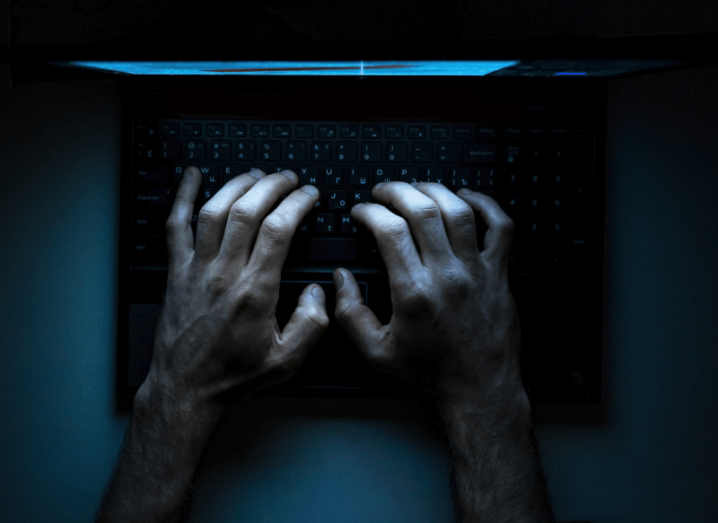 Hands typing on a computer keyboard in a dark room.