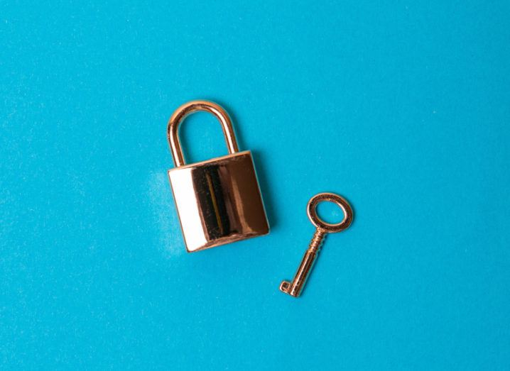 A rose gold padlock and key lie separately on a bright blue background at jaunty angles.