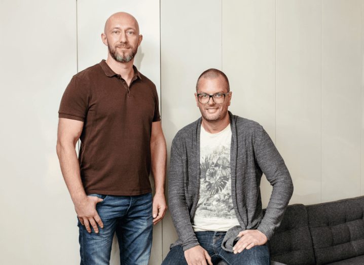 Two men with shaved heads standing in front of a white wall. The man on the left is wearing a burgundy shirt and the man on the right is wearing a grey cardigan with a white T-shirt.