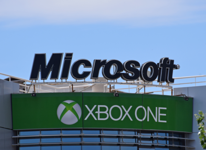 The Microsoft logo on top of an office building, over a sign for the Xbox One.