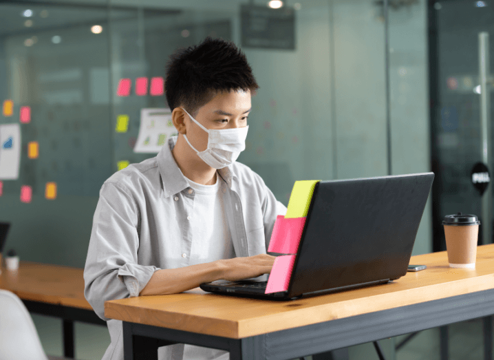 A person typing on a laptop while wearing a white mask.