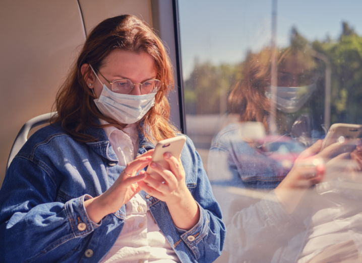 A woman wearing a denim jacket and a white mask on her face sits on a bus holding a smartphone.