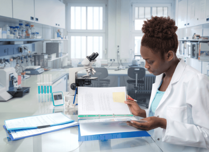 A woman in a white lab coat, sitting in a research lab reading papers.