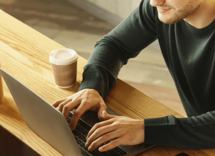 A man wearing a green sweater, using a laptop and drinking a coffee at a wooden table.