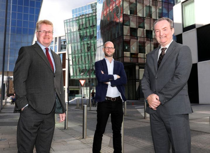Three men in suits from Tekenable and Greenfinch are standing and smiling into the camera in an outdoor setting in Dublin.