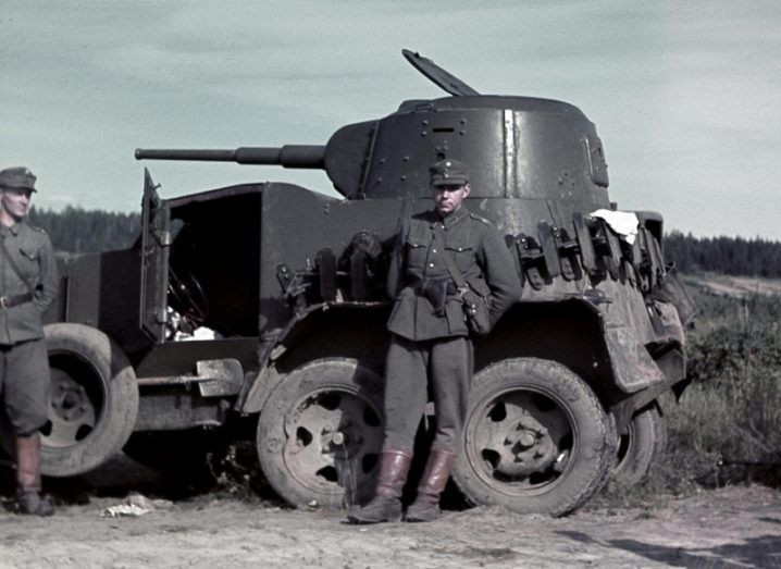 A Finnish soldier stands in front of a seized BA-10 armoured vehicle.