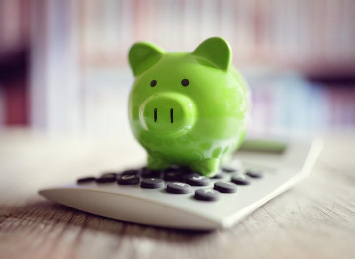 A green piggy bank on top of a calculator.